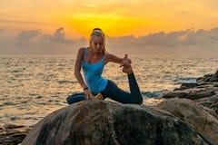 De jonge yoga van vrouwenpraktijken op de rotsen dichtbij het overzees bij dageraad op een tropisch eiland Royalty-vrije Stock Afbeeldingen