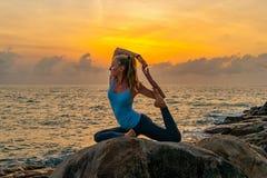 De jonge yoga van vrouwenpraktijken op de rotsen dichtbij het overzees bij dageraad op een tropisch eiland Royalty-vrije Stock Foto's