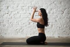 De jonge yogivrouw in vajrasana stelt met namaste, zolderachtergrond royalty-vrije stock foto's