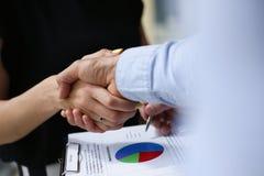 De jonge zakenlieden maken overeenkomstenhanddruk Stock Fotografie
