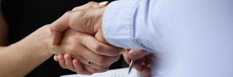 De jonge zakenlieden maken overeenkomstenhanddruk Stock Foto's
