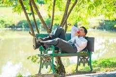 De jonge zakenlieden rusten op stoelen en eten daarna appelen royalty-vrije stock foto's