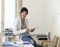 De jonge in zakenman in beanie en koele hipster informeel kijken zitting op huisbureau gebruikend digitaal gelukkig tabletstootku Royalty-vrije Stock Afbeelding