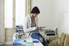 De jonge in zakenman in beanie en koele hipster informeel kijken zitting op huisbureau gebruikend digitaal gelukkig tabletstootku Stock Fotografie