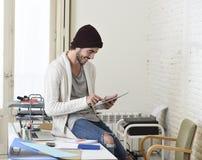 De jonge in zakenman in beanie en koele hipster informeel kijken zitting op huisbureau gebruikend digitaal gelukkig tabletstootku Stock Foto's