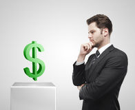 De jonge zakenman bekijkt de groene dollar van de V.S. sig Royalty-vrije Stock Afbeeldingen