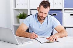 De jonge zakenman in blauw polooverhemd ondertekent een contract stock fotografie