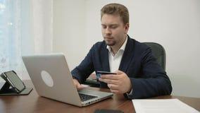 De jonge zakenman doet het online winkelen in zijn bureau die een creditcard houden en zijn aantal in de website typen stock video