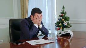 De jonge zakenman in een kostuum wrijft zijn neus, geen idee en vermoeid heeft kijken neer Wij begrijpen van zijn gezicht dat hij stock videobeelden