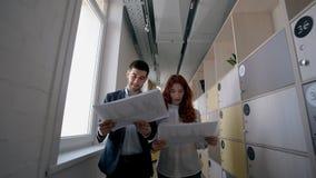 De jonge zakenman en de vrouw spreken over project, lopend in groot bedrijf stock videobeelden
