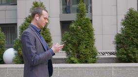 De jonge zakenman gaat met draadloze hoofdtelefoons in zijn oren en draait een bericht in smartphone stock videobeelden
