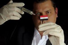 De jonge zakenman geeft een financiële injectie aan Egyptische vlag i stock afbeeldingen