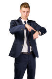 De jonge zakenman gekleed in een kostuum richt aan op horloge Royalty-vrije Stock Afbeeldingen