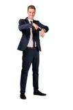De jonge zakenman gekleed in een kostuum richt aan op horloge Stock Afbeeldingen