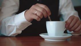 De jonge zakenman giet suiker in een mok met koffie, close-up stock videobeelden