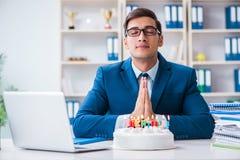 De jonge zakenman het vieren verjaardag alleen in bureau royalty-vrije stock foto