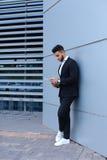 De jonge zakenman houdt en bekijkt documenten, bevindt zich dichtbij muur van royalty-vrije stock foto