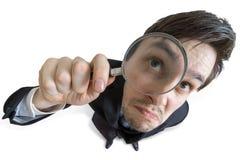 De jonge zakenman kijkt door vergrootglas Geïsoleerdj op witte achtergrond Mening van hierboven Stock Foto's