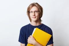 De jonge zakenman kleedde zich terloops, eyewear dragen, hebbend modieus kapsel, die in handen gele omslag met documenten of docu stock fotografie