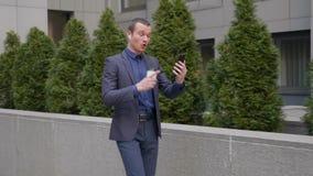 De jonge zakenman komt met draadloze oortelefoons en leidt agressief een bespreking over een videogesprek op smartphone stock videobeelden