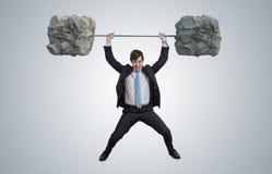 De jonge zakenman in kostuum heft zware gewichten op royalty-vrije stock foto