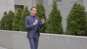 De jonge zakenman loopt met draadloze hoofdtelefoons in zijn oren en spreekt bij het videogesprek op smartphone stock footage