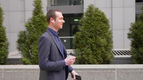 De jonge zakenman loopt onderaan de straat en spreekt op de telefoon in zijn draadloze hoofdtelefoons met koffie en een smartphon stock video