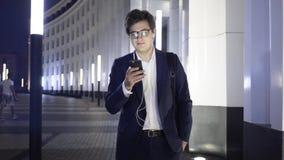 De jonge zakenman met een smartphone en hoofdtelefoons loopt in een straat van de nachtstad stock videobeelden