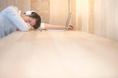 De jonge zakenman neemt een dutje in werkruimte Stock Afbeelding