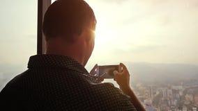 De jonge zakenman neemt foto met cellphone naast venster bij verbazende zonsondergang en mooie stadsmening Langzame Motie stock footage