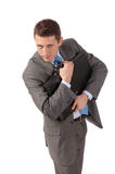 De jonge zakenman omhelst een portefeuille met vrees stock foto