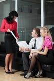 De jonge zakenman op kantoor met collega's stock foto