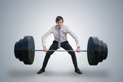 De jonge zakenman in overhemd heft zware gewichten op stock foto's