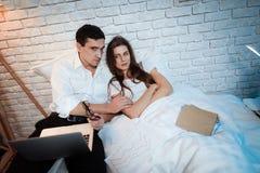De jonge zakenman probeert om vrouw te troosten De geïrriteerde vrouw is verstoord Het jonge paar debatteert royalty-vrije stock foto