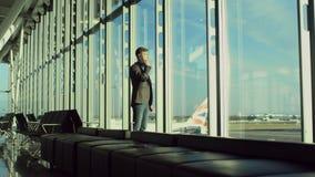 De jonge zakenman spreekt over een cellphone in luchthaven van Londen stock footage