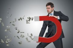 De jonge zakenman verzamelt geld met grote magneet stock foto