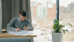 De jonge zakenman werkt aan project, gebruikend smartphone bij lijst in koffie stock videobeelden