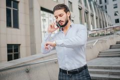 De jonge zakenman is zeer bezig Hij bekijkt horloges op zijn hand Ook gebaarde kerelbesprekingen op telefoon Hij loopt op stappen royalty-vrije stock foto's