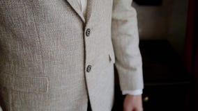 De jonge zakenman zet en maakt jasje aan door het venster recht stock footage