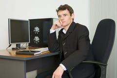 De jonge zakenman zit bij lijst Royalty-vrije Stock Foto