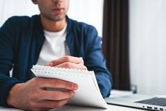 De jonge zakenman zit door lijst en maakt businessplan gebruikend blocnote en pen stock fotografie