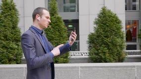 De jonge zakenmangang met draadloze oortelefoons en leidt agressief een bespreking over een videogesprek op smartphone stock videobeelden
