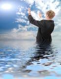 De jonge zakenmankosten in water en vragen van zon Stock Afbeelding