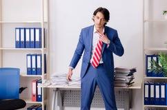 De jonge zakenmanwerknemer ongelukkig met het bovenmatige werk stock foto's