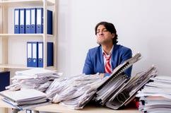 De jonge zakenmanwerknemer ongelukkig met het bovenmatige werk stock foto