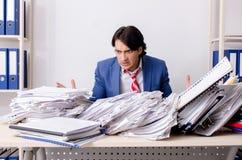 De jonge zakenmanwerknemer ongelukkig met het bovenmatige werk stock afbeeldingen