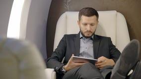 De jonge zekere advocaatzakenman gebruikt tabletzitting in het binnenland van het ondernemersvliegtuig stock videobeelden