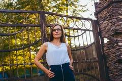 De jonge zekere bedrijfsvrouw met glazen bevindt zich op de straat dichtbij de ijzerdeur in de zomer Royalty-vrije Stock Afbeeldingen