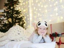 De jonge zitting die van het babymeisje dichtbij de magische Nieuwe giften van de jaarambacht door een Kerstboom dromen Royalty-vrije Stock Fotografie