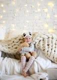 De jonge zitting die van het babymeisje dichtbij de magische Nieuwe giften van de jaarambacht door een Kerstboom dromen Royalty-vrije Stock Foto's